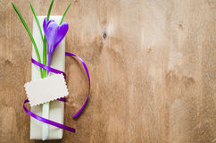 Present with fresh flower and blank note. Present with fresh flower and blank note on wooden table. Holidays background. Selective Focus Royalty Free Stock Photo