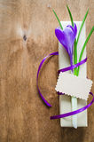 Present with fresh flower and blank note. Present with fresh flower and blank note on wooden table. Holidays background. Selective Focus Stock Photography