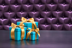 Present in front of a button tufted background Stock Photos
