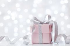 Present or gift box against bokeh background. Holiday greeting card on Birthday or Christmas. Present or gift box against white bokeh background. Holiday Royalty Free Stock Images