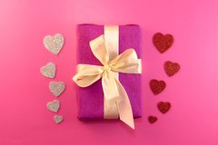 Present or gift box, paper heart and confetti on pink background top view. Valentines day greeting card. Flat lay style stock image
