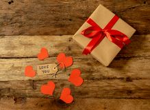 Present or gift box, paper red hearts and vintage wooden background top view for Valentines day stock images