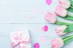 Present or gift box and pink flowers on blue wooden table top view. Greeting card for Womans or Mothers Day. Flat lay. Royalty Free Stock Photo