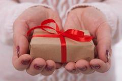 Present. Gift box. Woman holding small gift box with ribbon. Present. Gift box closeup. Woman holding small gift box with ribbon Stock Photos
