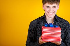 Present gift holding man looking camera Royalty Free Stock Photography