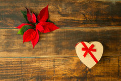 Present with heart shape and seasonal plant with red leaves Royalty Free Stock Images