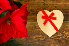 Present with heart shape and seasonal plant with red leaves Royalty Free Stock Photography