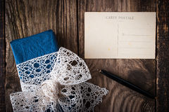Present with lace ribbon and postcard  horizontal. Present with lace ribbon and postcard on the wooden table  horizontal Stock Photos