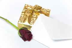 Present with letter and red rose Royalty Free Stock Photos