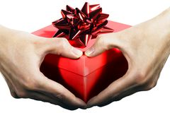 Present with love. Woman's hands forming a heart symbol, holding red gift box stock photos