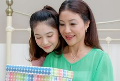 Present for mom,happy mother and young daughter hold present for Stock Photos