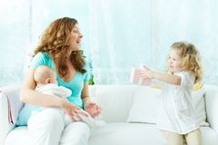 Present for mommy. Cute little girl surprising her mother with a present Royalty Free Stock Images