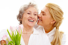 Present for mother. Portrait of pretty woman kissing and embracing her mother during holiday Stock Photo