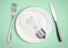 Present new idea concept. Light bulb on plate with fork and spoo royalty free stock photo