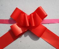 Present in recycled paper ecological. Red ribbon on the natural recycled grey paper Stock Photography