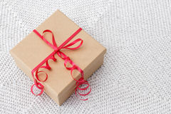 Present with red ribbon on a knitted background Royalty Free Stock Photography