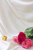Present and rose. On a silk background Stock Images