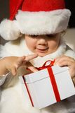 Present from santa. The small child presses to itself a beautiful  gift Royalty Free Stock Images
