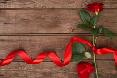 Present for St. Valentines Day - Red rose with  ribbon on dark wooden background  copyspace Royalty Free Stock Images