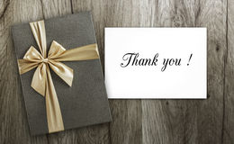 Present and Thank you card on wood. Present box and Thank you card on wood, top view Stock Photo