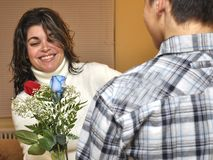 Latin family celebratin Mothers Day. Teenager boy. A teen gives flowers to his mom on a special occassion they are celebrating at home. Red rose and blue rose Stock Image