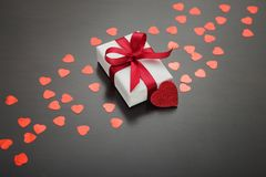 Present for Valentine`s day, Mother`s day or Wedding, wrapped in white paper, red bow and surrounded by red hearts. Stock Photo