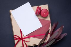 Present white card and gift in box with satin ribbon on dark background royalty free stock photography