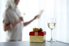 Present and wineglass for special occasion. Close up focus on colorful wrapped gift box and glass of champagne on table. Pensive woman is standing near window Stock Image