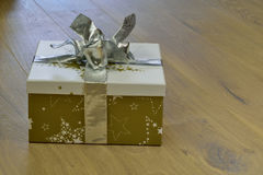 Present on a wooden floor. Christmas present on a wooden floor with silver colored ribbon Stock Photos