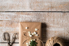 Present wrapped in brown paper, lilac flower laid on it. Studio Royalty Free Stock Photography