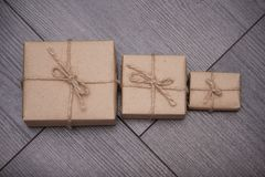 Present wrapped in craft paper with sack rope on wooden background. Smaller or bigger. Concept stock photos
