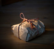 Present wrapped in newspaper. A present wrapped in old style in a newspaper and a fiber rope, on a wooden surface Royalty Free Stock Images