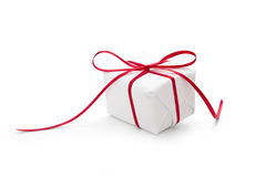 Present wrapped in white paper and tied with red ribbon Royalty Free Stock Photo