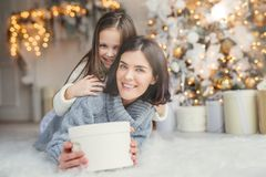 This present is for you! Happy small kid embraces her affectionate mother who holds wrapped present, stands against decorated back stock photo