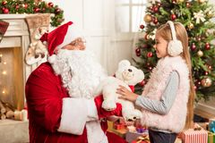 Grateful girl taking gift from Santa Claus. This present is for you. Kind senior bearded men in red and white costume is giving teddy bear to child. Girl is stock photos