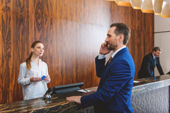 Presentable man standing at reception desk stock photography