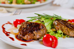 Presentable Plating of Roasted Meats with Veggies. Close up Presentable Plating of Tasty Roasted Meats with Lettuce, Tomatoes and Rosemary on White Round Plate royalty free stock photography