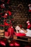 Presentación año del bebé 4-5 en sitio sobre el árbol de navidad con las decoraciones mirada de la cámara Feliz Navidad El Dr. el Imagen de archivo