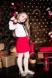Presentación año del bebé 4-5 en sitio sobre el árbol de navidad con las decoraciones mirada de la cámara Feliz Navidad El Dr. el Imagen de archivo libre de regalías