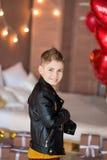 Presentación adolescente del inconformista hermoso con el baloon rojo del corazón en estudio Hombre joven en la camisa amarilla q Foto de archivo