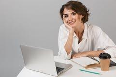 Presentación alegre feliz de la mujer de negocios aislada sobre el fondo gris de la pared que se sienta en la tabla usando el ord foto de archivo