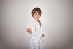 Presentación blanca del kimono del niño del karate que lleva Foto de archivo
