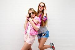 Presentación de dos amigos Forma de vida moderna Dos mejores amigos atractivos elegantes de las muchachas del inconformista listo Imágenes de archivo libres de regalías