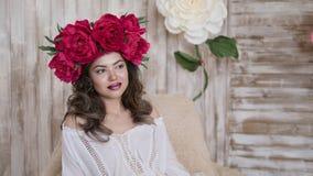 Presentación del modelo de la muchacha una mujer joven en una guirnalda de las peonías del escarlata en su cabeza, pelo rizado la Foto de archivo