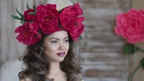 Presentación del modelo de la muchacha una mujer joven en una guirnalda de las peonías del escarlata en su cabeza, pelo rizado la Fotografía de archivo