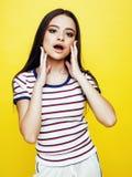 Presentación enojada de la mujer bastante adolescente de los jóvenes en el fondo amarillo, concepto de la gente de la forma de vi Foto de archivo libre de regalías