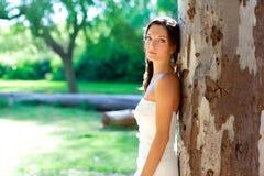 Presentación feliz de la mujer de la novia en árbol al aire libre Imagen de archivo libre de regalías