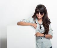 Presentación feliz de la mujer joven con la cartelera en blanco blanca Fotografía de archivo