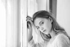 Presentación femenina caucásica del modelo de moda Muchacha bonita con los ojos azules que se colocan en la ventana Imagenes de archivo