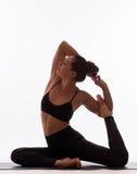 Presentación femenina de la yoga hermosa joven en un fondo del estudio foto de archivo libre de regalías